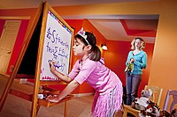 Little girl, age 6 writing on board and mom standing by in awe