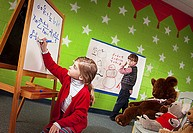 Little girl writing amazing math problem on board while boy looks on in amazement