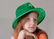 This beautiful green eyed, 9 year old Caucasian girl is wearing a green St Patrick´s Day hat in a closeup on a light background Her facial expression ...