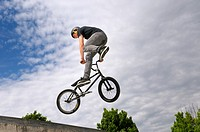 BMX bike rider exiting a bowl air out with a Tail Whip 360 spin