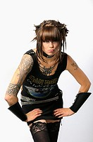 Young pouting heavy metal lady with horns piercings and tattoos on a white background