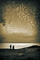 Couple walking on beach in winter