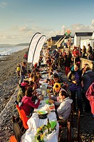 People sitting at tables at the annual al fresco dinner on the beach, summer evening, Borth village, Ceredigion Wales ULK