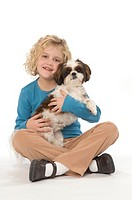 A seven year old girl with her Shih Tzu dog, smiling and looking at viewer