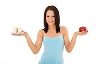Caucasian woman holding an apple and slice of cake trying to decide which one to eat