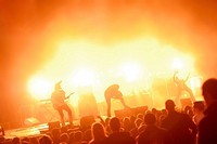 Rock band playing live on stage to audience, with colorful lighting, generic or anonymous concept image