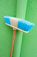 Household broom leaning against lime green wall of house in Burano island near Venice Italy