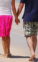 Couple holding hands, walking on beach