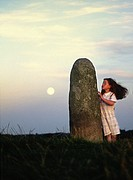The Lia Fail, crowning stone of the high kings of Ireland, full moon rising  Ancient ritual site of Tara, County Meath, Ireland. The picture shows a l...