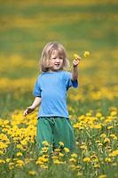 boy with long hair standing in a dandelion field