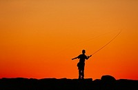 Boy fishing from a jetty at sunset, Menemsha, Martha´s Vineyard
