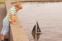 A small boy sailing his toy boat at the boating lake in Aldeburgh , Suffolk , Uk