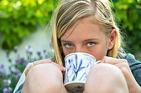 Close up of teenage girl with a cup of soup in the garden.
