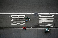 Pedestrians walk past a BUS ONLY street sign in Manhattan