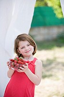Caucasian girl holding a bowl with nice strawberries