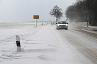 Cars drive on a Street with snow banks