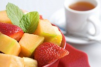 Fruit Salad in a red bowl with a cup of tea