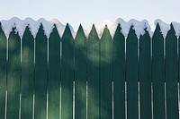 Some snow on a green fence