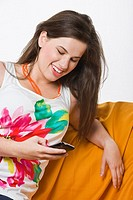 Young woman using mobile phone sitting on sofa smiling