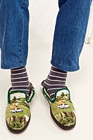 Two feet in striped socks and funny comfortable slippers retirement and comfort concept
