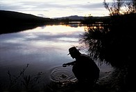 Sweden, Lapland, Ammarnas region, Man drinking pure water from a river