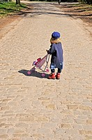 small child alone with a baby carriage in the street, 2 years old