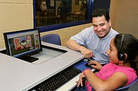 Armando Rios of the Boys and Girls Club helps Graciela Diaz on the computer in Tucson, Arizona, USA