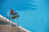 A partial view of a motel swimming pool showing water and an empty life guard stand.