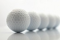 A line of 5 reflected golf balls on a white background