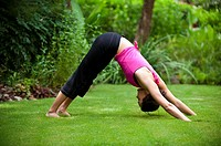 25 year old brunette woman in a garden settng wearing work out clothing doing  the yoga pose downward facing dog.