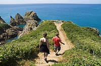 Jerbourg Point ST MARTIN GUERNSEY Young tourist couple footpath Pea stacks Les Tas de Pois and rocky headland