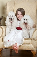 Shot of a Happy Blonde Girl in Large Armchair with Two White French Miniature Poodles