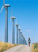 Woman walking on track beside wind turbines, part of the massive wind farm complex at Altamont near Livermore, California, USA