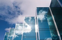 Five towers of a sleek modern glass office building in Silicon Valley with the clouds and sky reflecting on the surface of the buildings. San Mateo, C...