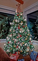 This beautiful stock image is a vertical shot of an indoor lighted and decorated Christmas tree with two windows reflecting the lights and decor, pres...