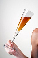 young Woman´s shoulder arm and hand holding a cocktail glass at an event