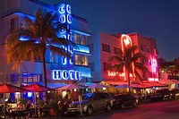 Art deco hotels at night with neon lights along Ocean Drive, in the Art Deco District of South Beach, Miami, Florida  People are eating at the sidewal...