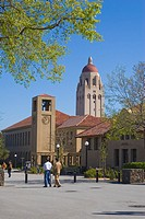 People walking on a street on the Stanford University campus, with Hoover Tower overlooking the clock tower and at the school of education  The sandst...
