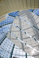 Looking up at the glass dome of the San Jose City Hall rotunda building  The shadows are making patterns on the sails stretching across the dome as th...