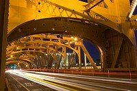 Lights from cars traveling across the gold steel structure of Tower Bridge at night in Sacramento, California  The bridge is a vertical lift bridge an...