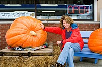 Susan Zavodny of Barrington, IL next to a huge pumpkin at a gas station in Sister Bay, Wisconsin  If you guess the exact weight of the pumpkin you win...