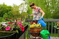 Woman potting flowers on back porch deck
