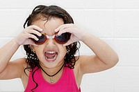 Little girl in swim suit and swim goggles with excited look on her face.