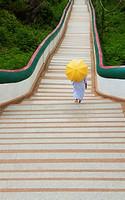 nun walks down long stairs at Wat Phra Phuttabat outside of Khon Kaen, Thailand