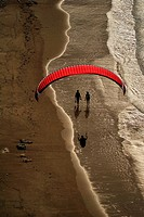 Paragliding and couples strolling on the beach Torimbia, Llanes, Asturias