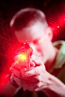 Ocala, FL - July 2009 - Young man pointing pistol with laser grip at camera