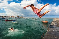 Children jumping in water at Muelle Don Luis. Castro Urdiales Bay, Cantabria, Spain.