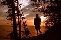 Woman hiking along Lake Michigan sand dune at sunset.