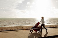 Mother and children with pushchair walking on promenade with sea as background
