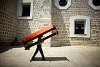 A man carries a church bench to the Basilica de la Soledad, or Solitude Basilica, after a holy week procession in Oaxaca, Mexico